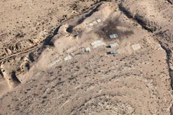 """LATITUDE: 31°16'17""""N / LONGITUDE: 34°59'48""""E, November 22, 2011. Remains of the foundations of the homestead of Ḥasan a-Sarāyʽa, of the Abu Jwēʽid tribe, on the outskirts of the unrecognized village of Bāt al-Sarāyʽa. The buildings were recently demolished; debris littered about the site indicates a forced evacuation. The area is now considered a closed military live-fire training zone. Despite the evacuation, two small structures—whose tin sheeting is held down with rocks—have been reconstructed atop the remains. The height of the structures casts its shadow upon the land. The site is on the land of Shlalīn, a Bedouin community evacuated in the aftermath of Operation Yo'av., from the series Desert Bloom"""