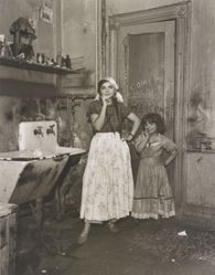 N.Y.C. 1940 [young woman and girl, dressed up, in kitchen with sink and graffiti on door]