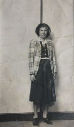 Standing woman in plaid jacket, striped background