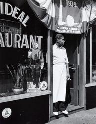 Harlem restaurant owner standing under 1939 New York World's Fair Poster