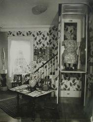 "Interior view of Katherine S. Dreier's Milford home, ""Laurel Manor"" -- KSD in elevator, sitting, frontal"