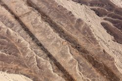 """LATITUDE: 30°45'14""""N / LONGITUDE: 35°10'31""""E, November 22, 2011. Impact craters and wreckage of two Israeli Air Force (IAF) Skyhawk planes used as targets along a simulated airstrip in the live-fire zone of the Naḥal Masor/Wādi Munshār (Heb./Arabic). The IAF uses dummy bombs−weights without explosives or detonation−to target the airstrip from above and register the accuracy. The hundreds of pockmarks across the soft surface of the canyon floor register the bombing runs. This portion of the Aravah desert lies below sea level and at the base of the tributaries of the Aravah stream. The nearby Moshav ʽEin Ḥatzeva was founded in 1965 by Naḥal soldiers to support Jewish settlement growth throughout Israel, particularly in the more remote areas of the country. Three years later, it became a civilian moshav., from the series Desert Bloom"""