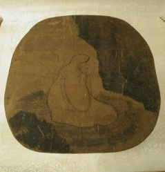 Daruma, seated meditating under a rock