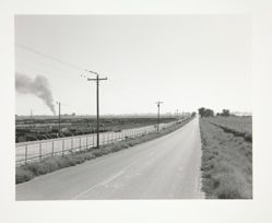 Open road with smoke on horizon, feed lot, Weld County, Colorado