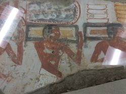 Wall painting fragment showing three offering bearers moving to the right
