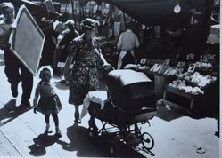A different version of woman with baby carriage in front of fruit stand