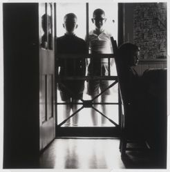 Untitled [Two boys standing behind screen door]