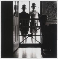 Untitled [Two boys standing behind screen door]