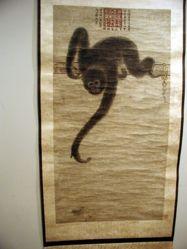 A Gibbon Reaching for a Lotus Pod
