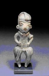 Standing male figurine wearing a flilleted skirt