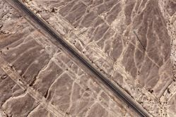 """LATITUDE: 30°25'53""""N / LONGITUDE: 34°56'26""""E, November 22, 2011. Traces of flooding and heavy vehicle paths alongside the north–south Highway 40 between Mitzpe Ramon and Eilat. The area shown is located within a seasonal stream in the Aravah desert mountains leading to the Ramon Crater. The tracks running by the side of the road are used by heavy vehicles and military convoys, and have shifted away the upper layer of alluvium which has been eroded, reshaped by water, and deposited again. The larger particles of sand and gravel here are comprised mainly of flint., from the series Desert Bloom"""