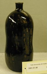 Tamba wine bottle with small short neck, in and out curving sides, flat base.