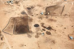 """LATITUDE: 31°06'60""""N / LONGITUDE: 34°43'4""""E, October 9, 2011. Abu Asa family homestead in the vicinity of the recognized Bedouin town of Bīr Haddāj, of the ʽAzāzme tribe. The dark circular stains in the center of the image indicate the former presence of sire, livestock pens for camels, goats, and sheep. Staining is created by the bodily fluids of the herds that were kept there. Each year, the pens are shifted and the former space disinfected by fire. The stains remain on the ground for several years, the gradient of their saturation indicating how many rainy seasons have washed them away. Such traces help gauge the minimum duration of their presence in years. In 1978 Bīr Haddāj was declared a closed military area, forcing its inhabitants to relocate to Wādi al-Naʽīm, near Beersheba. In 1994, when they learned that land on which they had previously settled was no longer used for military purposes, but had been converted into a moshav, they returned and settled beside the moshav., from the series Desert Bloom"""