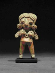 Standing female figurine with ear plugs and circular pendant