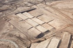 """LATITUDE: 31°3'25""""N / LONGITUDE: 34°50'48""""E, November 22, 2011. Earthworks in the construction of the Ariel Sharon Training Complex. Each of the separate tiers, graded above the desert floor, encircled by dirt paths that will become the main artery, is to support the foundation of a new building within the complex. Unofficially named ʽIr HaBahadim (lit., """"city of training bases""""), this mega-base is currently under construction between the development town of Yeruḥam and Beersheba, and is projected to become the Negev's third largest city. Planned for 30,000 army personnel, it is scheduled to open in 2015., from the series Desert Bloom"""