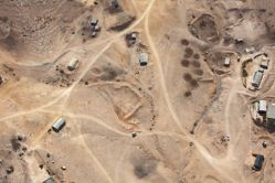 """LATITUDE: 30°58'57""""N / LONGITUDE: 34°57'52""""E, November 14, 2011. Bedouin homestead of the Habsi family, of the ʽAzāzme tribe, in the unrecognized village of Rakhma. Tin houses, dirt roads, and a number of sire are visible, as well as the herds being led along the top left corner. The village currently has approximately 1,500 residents, a portion of whom have lived here for generations. After the war of 1948, during which the majority fled, seventeen families remained. In 1956 the remaining residents were transferred from the Ovdat/ʽAbdāt region as internally displaced citizens. Rakhma is frequently cited as a village suitable for recognition by the state. In 2009 the village council turned to Bimkom, an Israeli organization established to encourage democracy and human rights in the field of planning, for help in arguing for recognition of the village by the state. Currently an unrecognized village, the homes are under constant threat of demolition and the village remains without electricity, paved roads, sewage facilities, or garbage disposal., from the series Desert Bloom"""