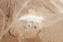 """LATITUDE: 31°1'11""""N / LONGITUDE: 34°43'50""""E, October 9, 2011. Remains of the demolished home of ʽAwad Abu Ḥbak, of the ʽAzāzme tribe, in the vicinity of the village of Bīr Haddāj. The home was demolished in 2006 and the family forced to move further east. Signs of heavy vehicles and scouring of the area are visible, with the structural remains and belongings strewn about the site. In 1978, Abu Ḥbak and the other members of Bīr Haddāj were evacuated by the military. In 2004, as part of the Israeli government's """"Abu Basma Plan"""" to sedentarize the Bedouins of the Negev, Bīr Haddāj and eight other Bedouin villages were officially recognized as Bedouin townships. But with the provisions of the plan deemed unacceptable to the Bedouins, no family has purchased land in accordance with the new mandate of the Israeli law., from the series Desert Bloom"""