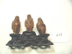 Three brown wooden figures on black wooden base