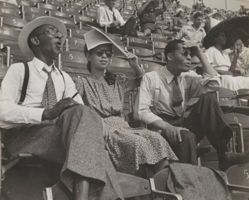 Ted Poston, with his wife and friend, enjoying a Sunday ball game at the Black Yankees field in Harlem.