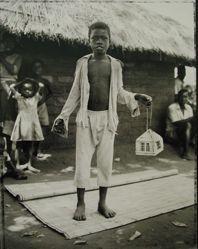 Tony Matayu with caged Kambuna birds, Mozambiquan refugee camp, Nyamithuthu, Malawi